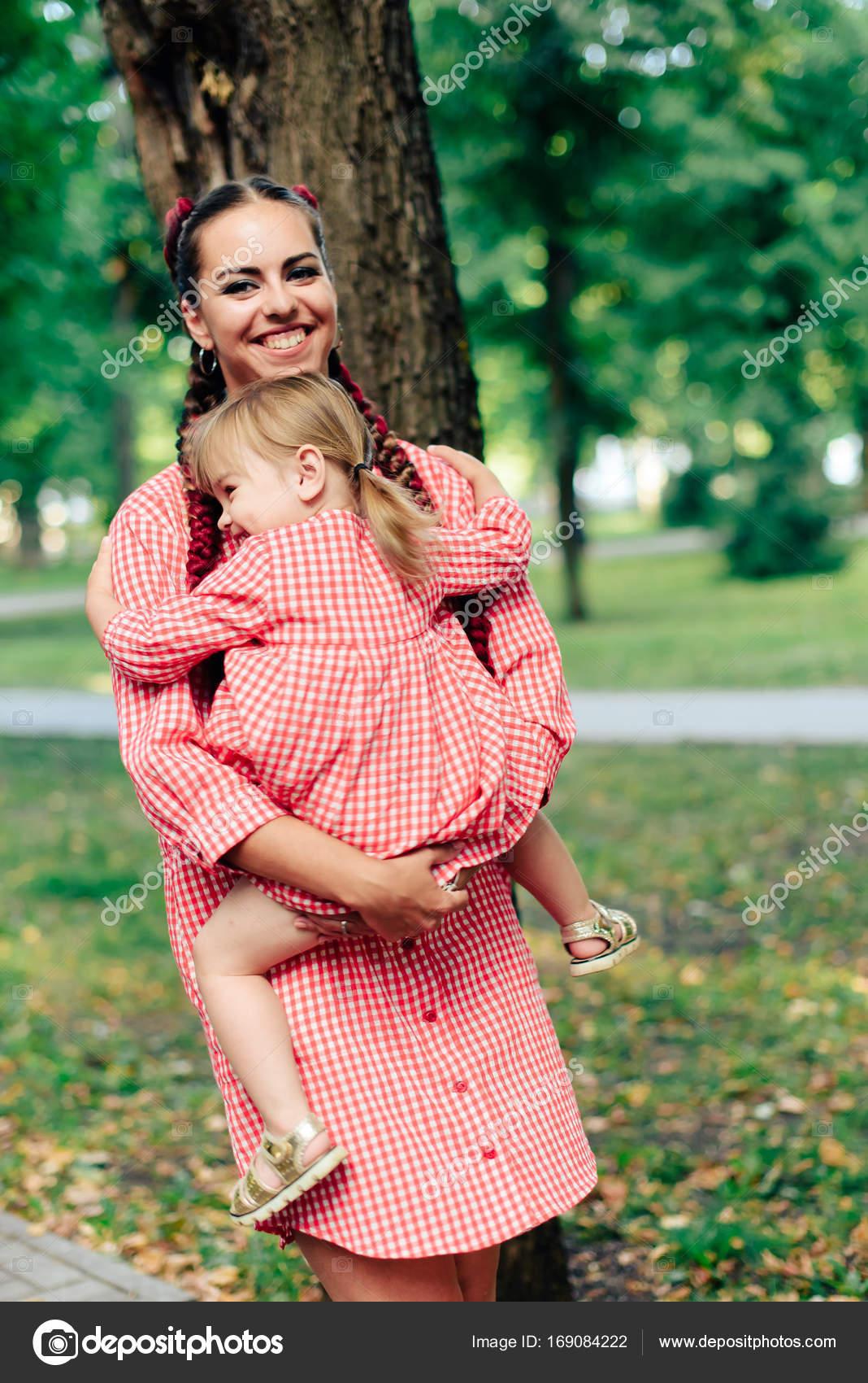528b86506 Familia joven feliz con bella bebé con ojos azules camina en el parque de  verano al atardecer. Vestidos de mamá y la hijita de idéntico color rosa 1  — Foto ...