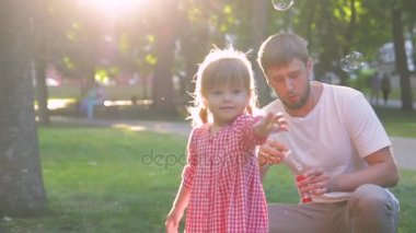 young happy family with little beautiful baby with blue eyes walking in summer park at sunset.