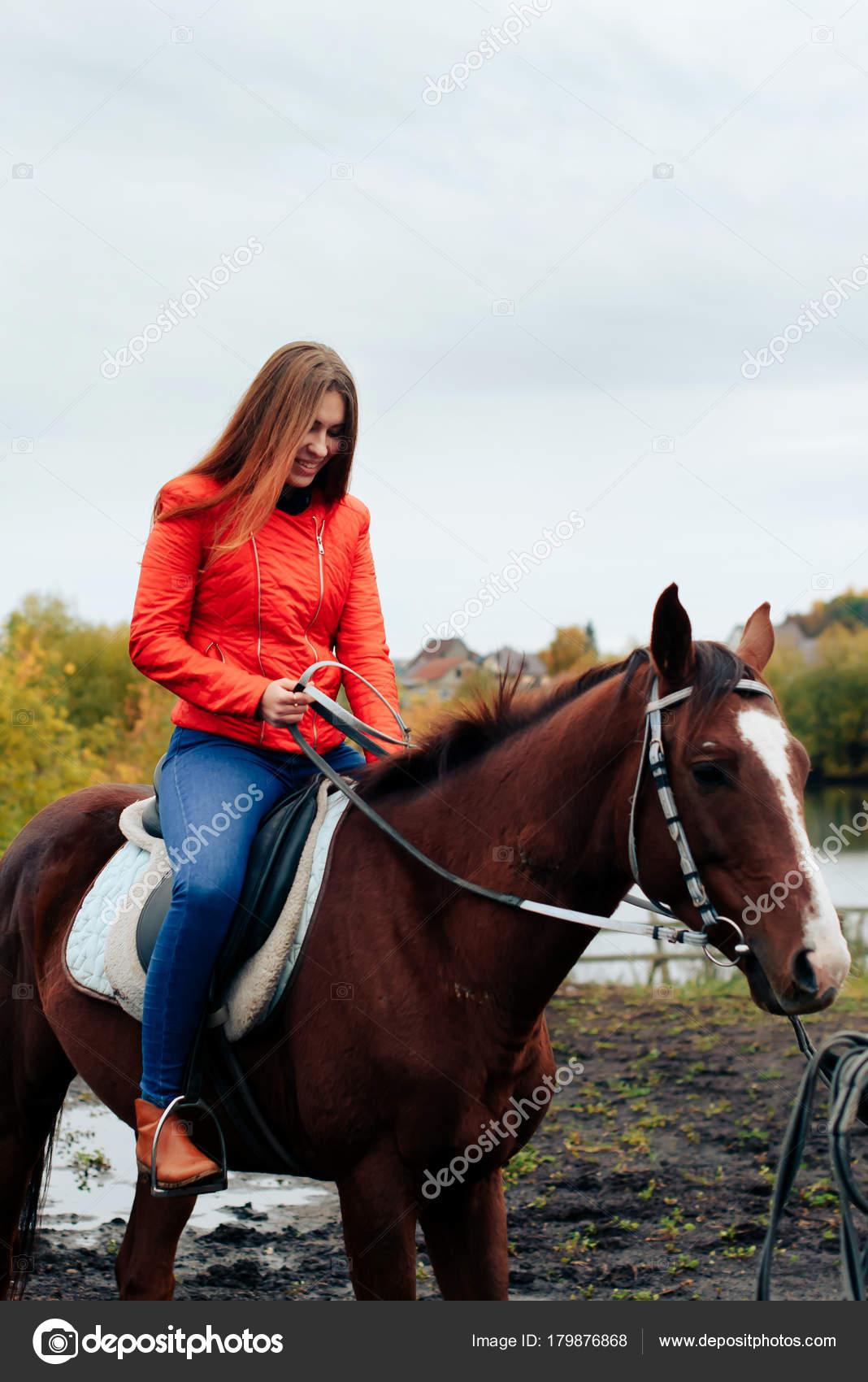 schönes mädchen reitet auf einem pferd in einem dorf im
