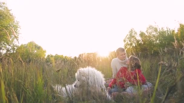 young couple walking in the summer park with a white dog