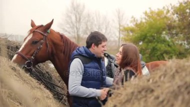 young couple in a Russian village with horses, riding