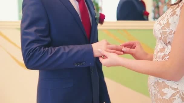 the bride puts on an engagement ring on the grooms finger
