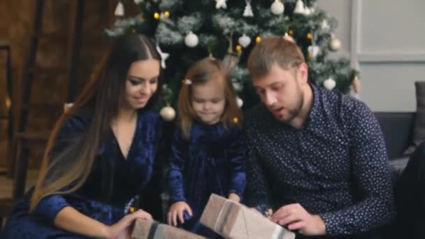 Happy family around the Christmas tree with gifts