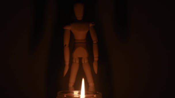 hölzerne Puppe auf einem schwarzen Hintergrund Licht einer Kerze in einem Glas
