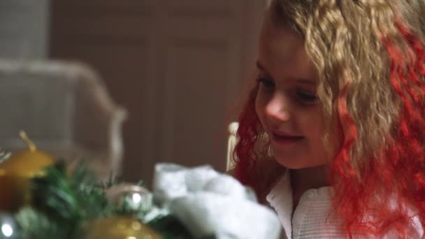 little beautiful girl on the background of a decorated Christmas tree with lights