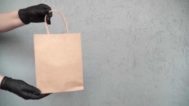 kurýr předá s produktem řemeslný balíček kupujícímu, bezkontaktní doručení jídla a dalšího zboží