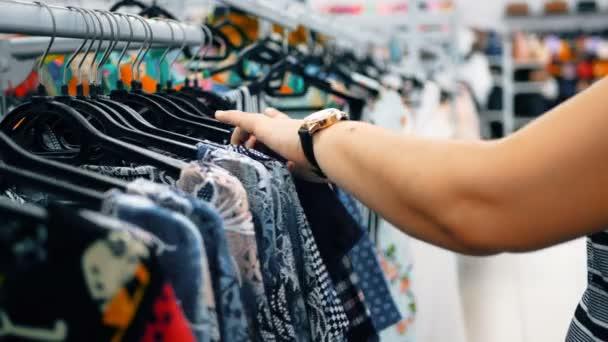 Žena zvolí šaty v obchodech oblečení. Detailní záběr rukou