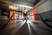 Fotografie Junge fit Mann mit Schlacht Seile in das Fitness-Studio trainieren