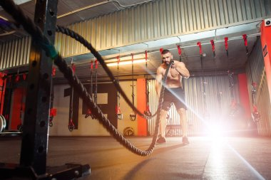 Young fit man exercising with battle ropes in the fitness gym
