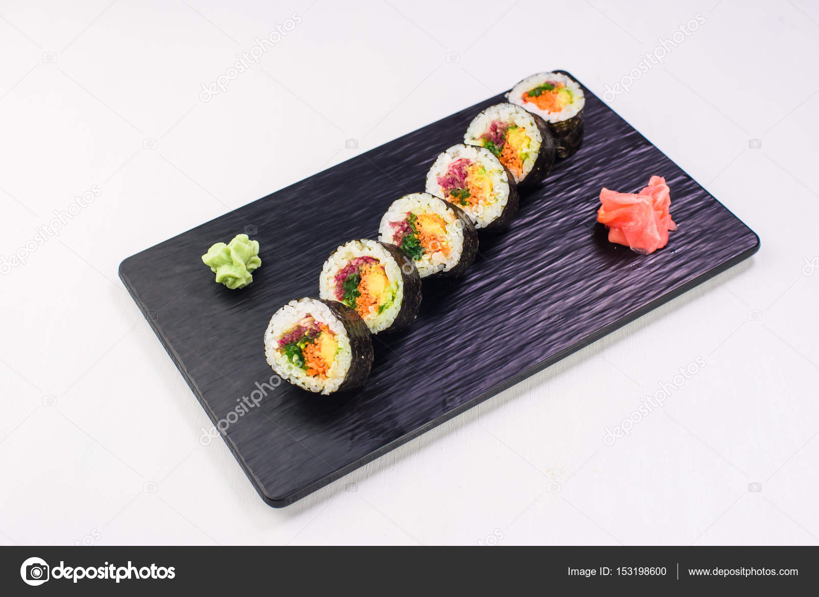 vegetarian rolls and sushi on a black stone plate top view stock