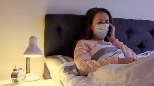 Kranke Frau mit medizinischer Maske auf dem Gesicht liegt zu Hause im Bett, hustet und ruft einen Arzt. Frau mit Coronavirus-Symptomen. Covid-19-Infektion.