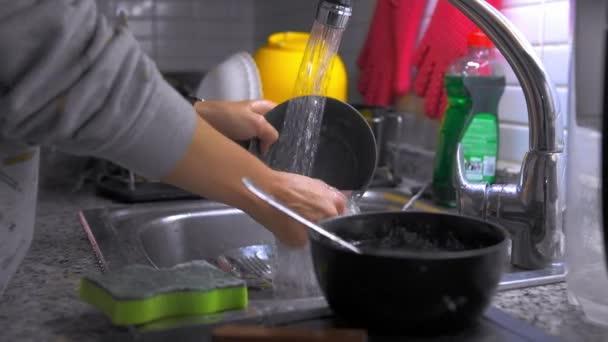 Ženy si doma důkladně myjí nádobí v kuchyňském dřezu. Mytí nádobí, domácí práce.