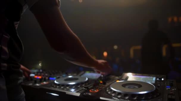 DJ egy éjszakai klubban működik, keveri a zenét egy távirányítóval