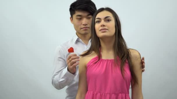 Ázsiai fiú bemutatja Valentin kártya lány fehér alapon