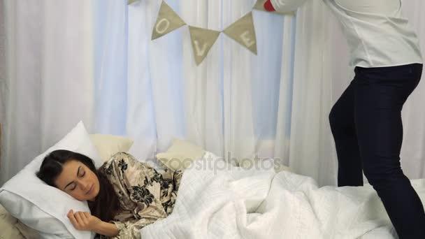 Mladý muž dělá překvapení pro svou přítelkyni na Valentýna, zatímco ona spí