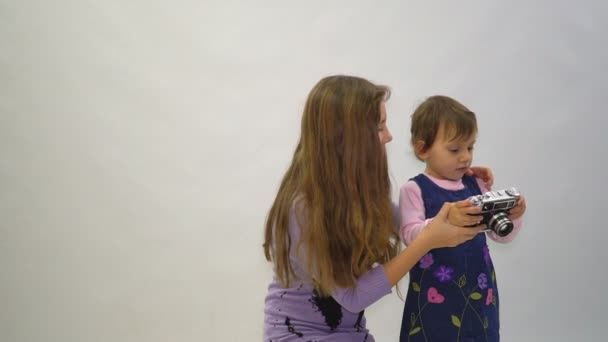 Little girl and her elder sister with a vintage photo camera ona white background