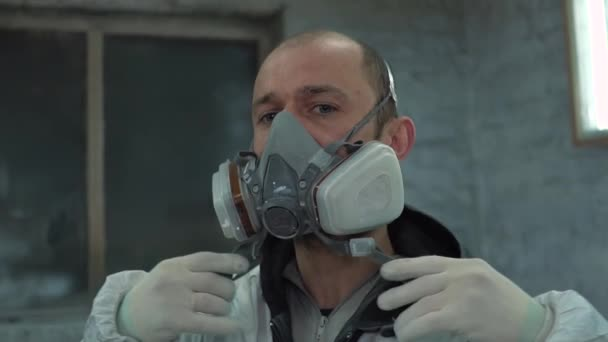 Man puts on the mask before painting the car