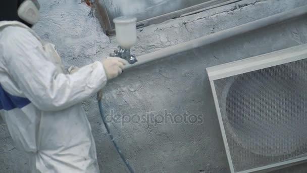 Painter checks the spray gun near the ventilation in the spray booth