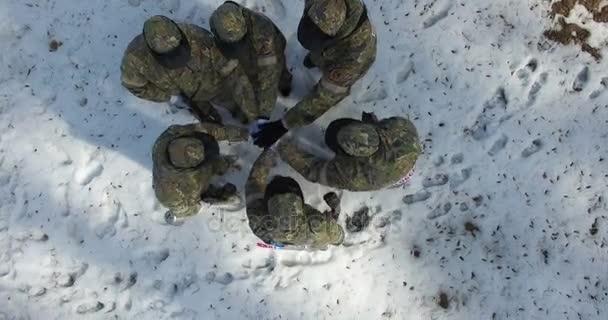 Stojící v kruhu kluci v maskování lepení ruce pro zahájení boje