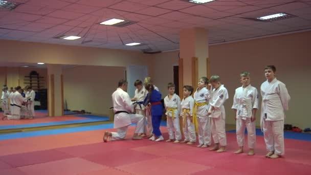 Kiev, Ukrajna - 2017. február 6.: Karate-képzés és az edző segít a gyerek a megfelelő ruha, öv a kimonó