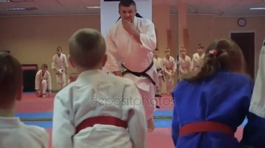 KIEV, UKRAINE - February 6, 2017: Coach speaks and kid students stand up after speech about rules training