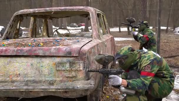 Kyjev, Ukrajina - 4 března 2017: Chlap v masce paintball s pistolí střílí z přístřešek na auto