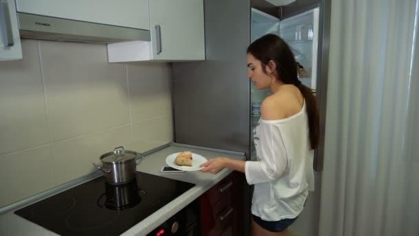 Mädchen ist am Telefon sprechen, bevor sie den Kuchen in den Kühlschrank legt