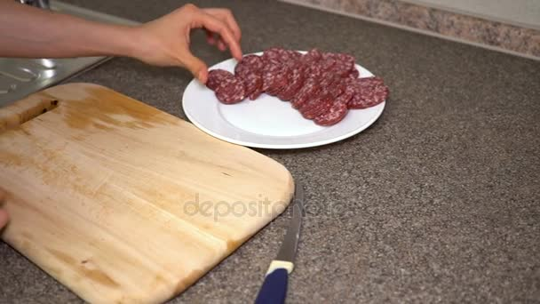 Girl puts salami for sandwiches on a plate