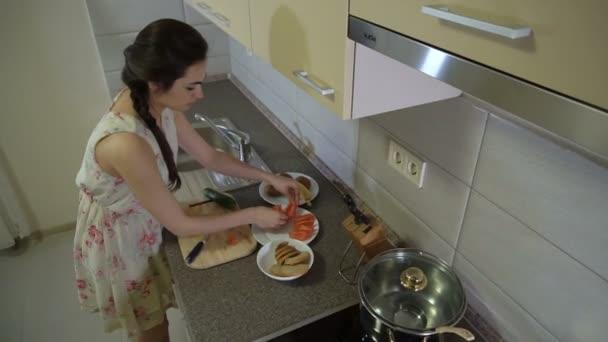 Girl brunette is putting sliced vegetables on a plate