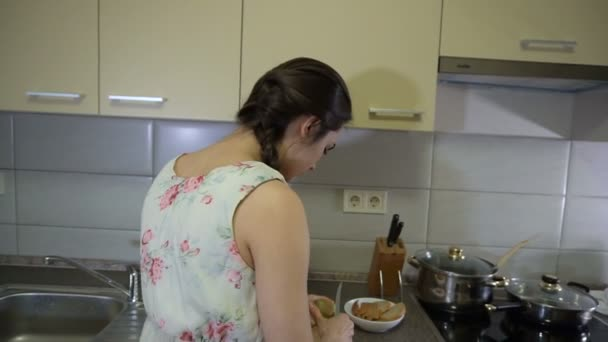 Brunette girl prepares vegetables and fruit and sings a song
