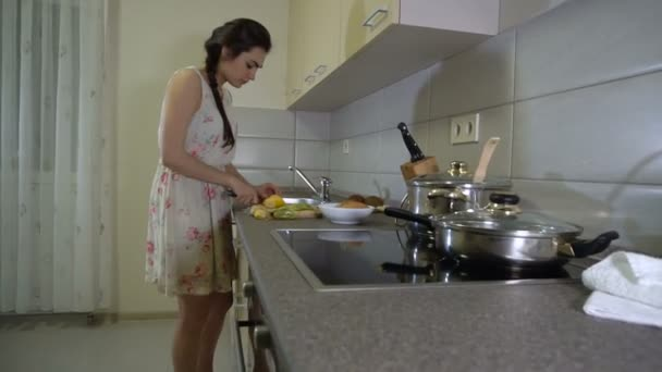 Girl is slicing fruit in the kitchen