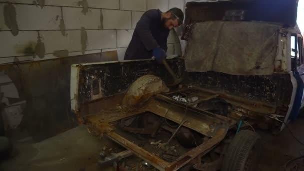 Pracovníka autoservis bije rezavé Auto tělo pomocí kladivo