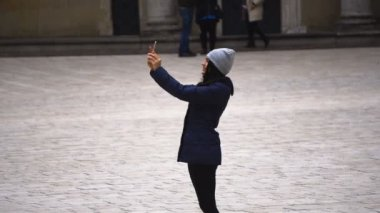 Girl makes selfie is standing on the square