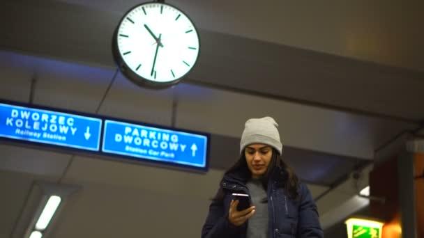 Holka s rovnátkama čeká příjezd vlaku a mluví o telefonu