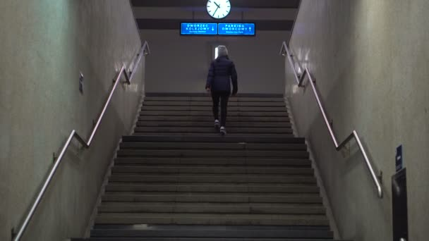 Girl climbs the stairs to the platform of the railway station