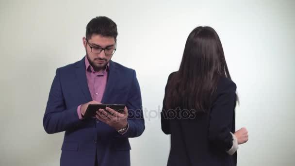 Obchodní partnery člověk se dívá na tabletu a dívka po tanec dostane peníze vyhrál v sázce od kolegu
