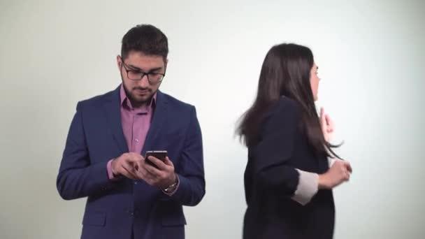 Obchodní partnery člověk se dívá na smartphone a dívka po tanec dostane peníze vyhrál v sázce od kolegu