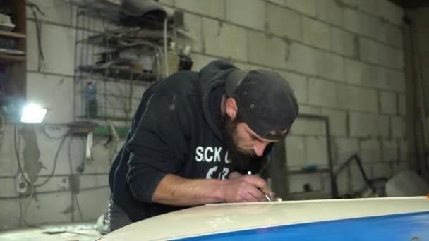 Mechanik pro dospělé vousatý muž soustřeďuje Malování airbrush na kapotě auta