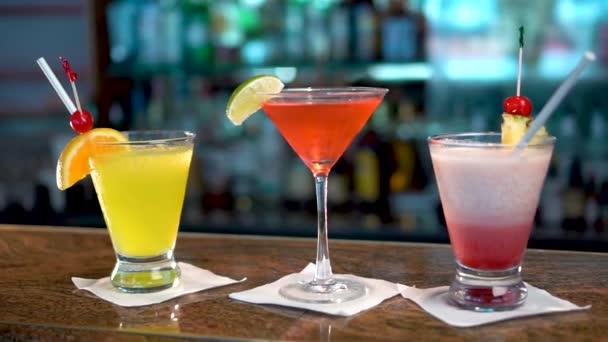 drei Gläser mit bunten alkoholischen Getränken auf einem Bartresen, Großaufnahme von Cocktails