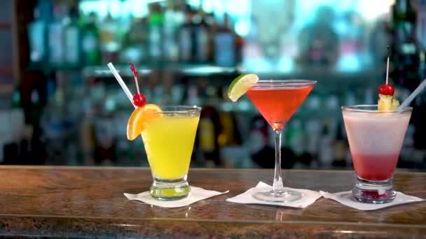 drei Gläser mit bunten alkoholischen Getränken auf der Theke, Großaufnahme von Cocktails