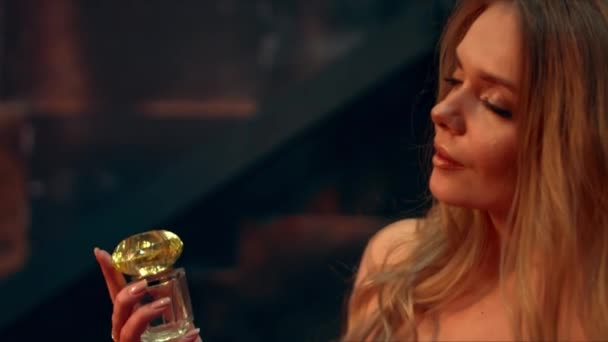Beautiful girl holds a bottle of perfume