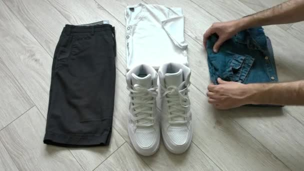 Mens casual outfits including dark blue shorts, white shirt, denim shirt, white sneakers and accessories. Flat lay, top view.