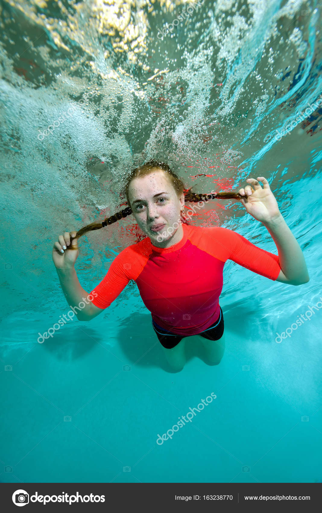 Junges sportliches Mädchen schwimmt unter Wasser auf