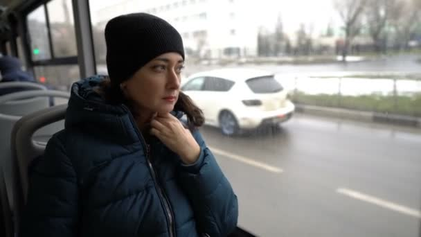 An adult Oriental girl sits and looks out the window of a bus that is traveling through the city. Outside the window, cars are driving, houses and people are flashing by. View from inside the bus. 4K.