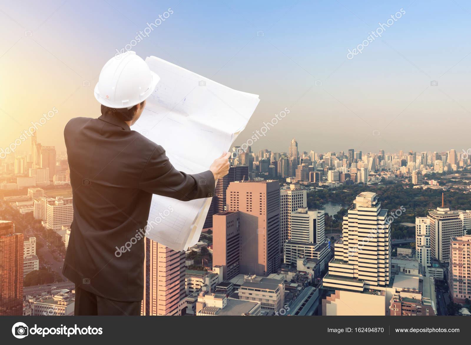 Consultora con ingenieros trabajando y holding blueprint ingeniero consultora con ingenieros trabajando y holding blueprint ingeniero diseador con plan de explotacin de casco en su mano para el plan de gestin de malvernweather Choice Image