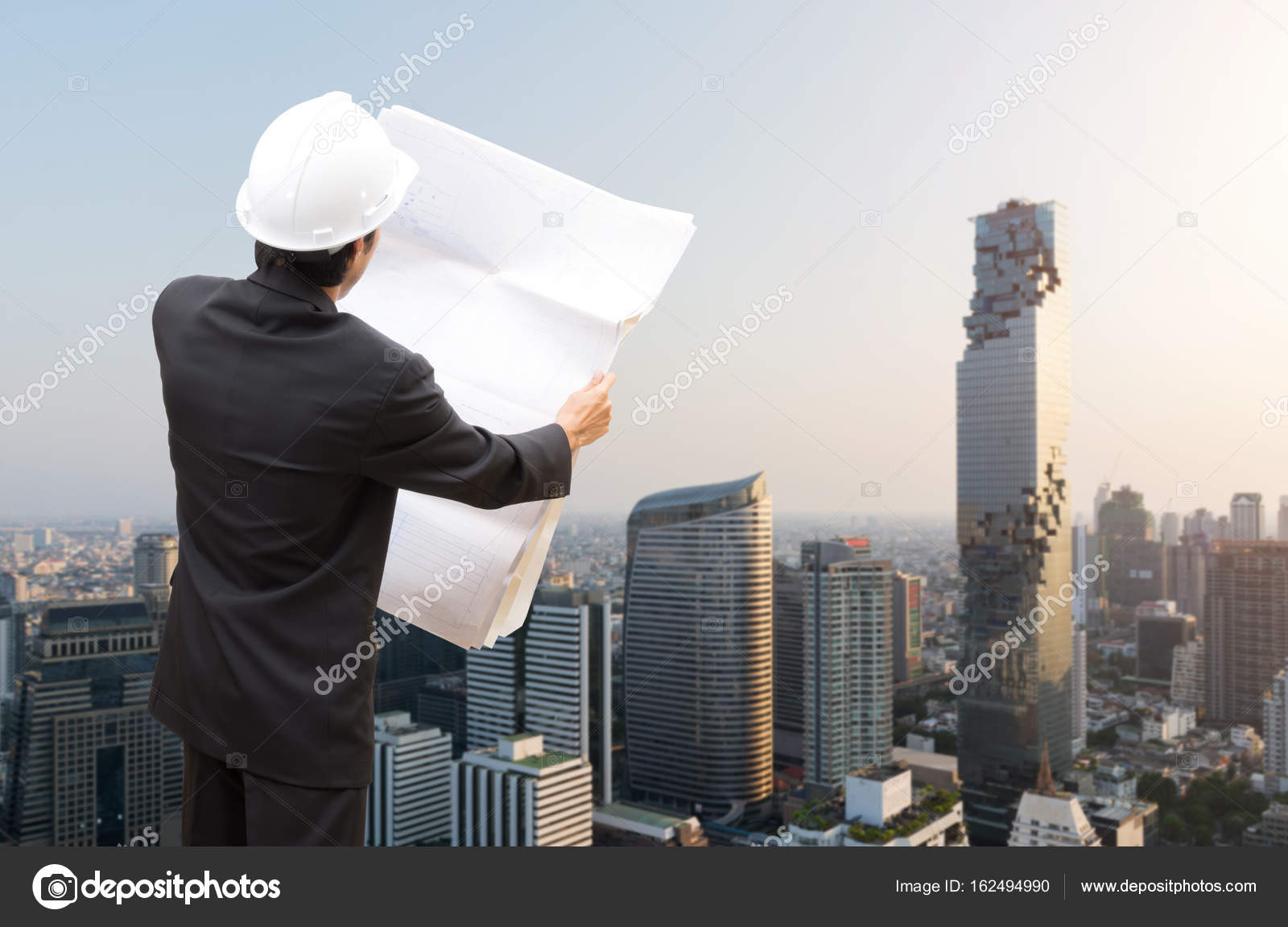 Management consulting with engineers working and holding blueprint management consulting with engineers working and holding blueprint engineer designer with helmet holding blueprint in his malvernweather Choice Image