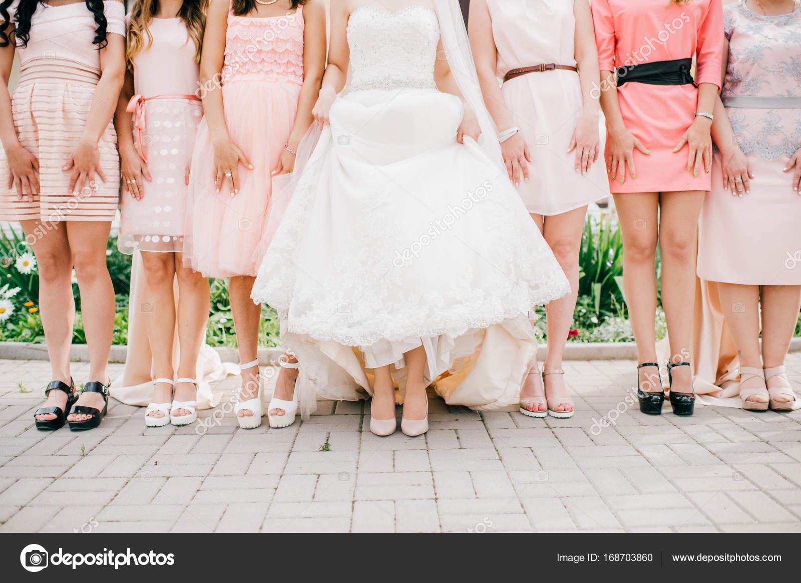 Glückliche Braut mit sechs Freunden, die auf dem Boden stehen ...