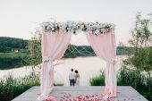 Happy bride and groom after ceremony sitting at wooden place for wedding arch with decor and flowers. Rose petals and lawn. Couple of lovers embracing at sunset near lake. Head on shoulder. Romantic.