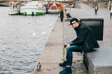 Lonely man sitting on bench in depression and thinking of problems in life. Abstract city background. Dove walking the embankment river in Prague. Psychological male portrait. Solitude and loneliness.