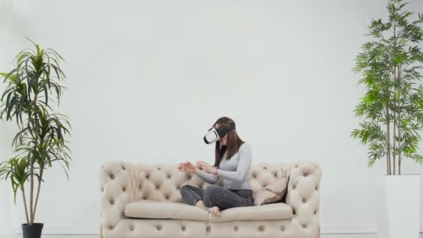 Caucasian girl interacting with virtual environment using VR glasses (goggles)